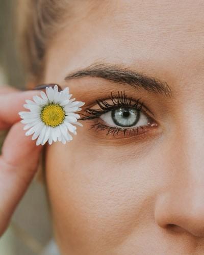 Woman wearing mascara while holding flower